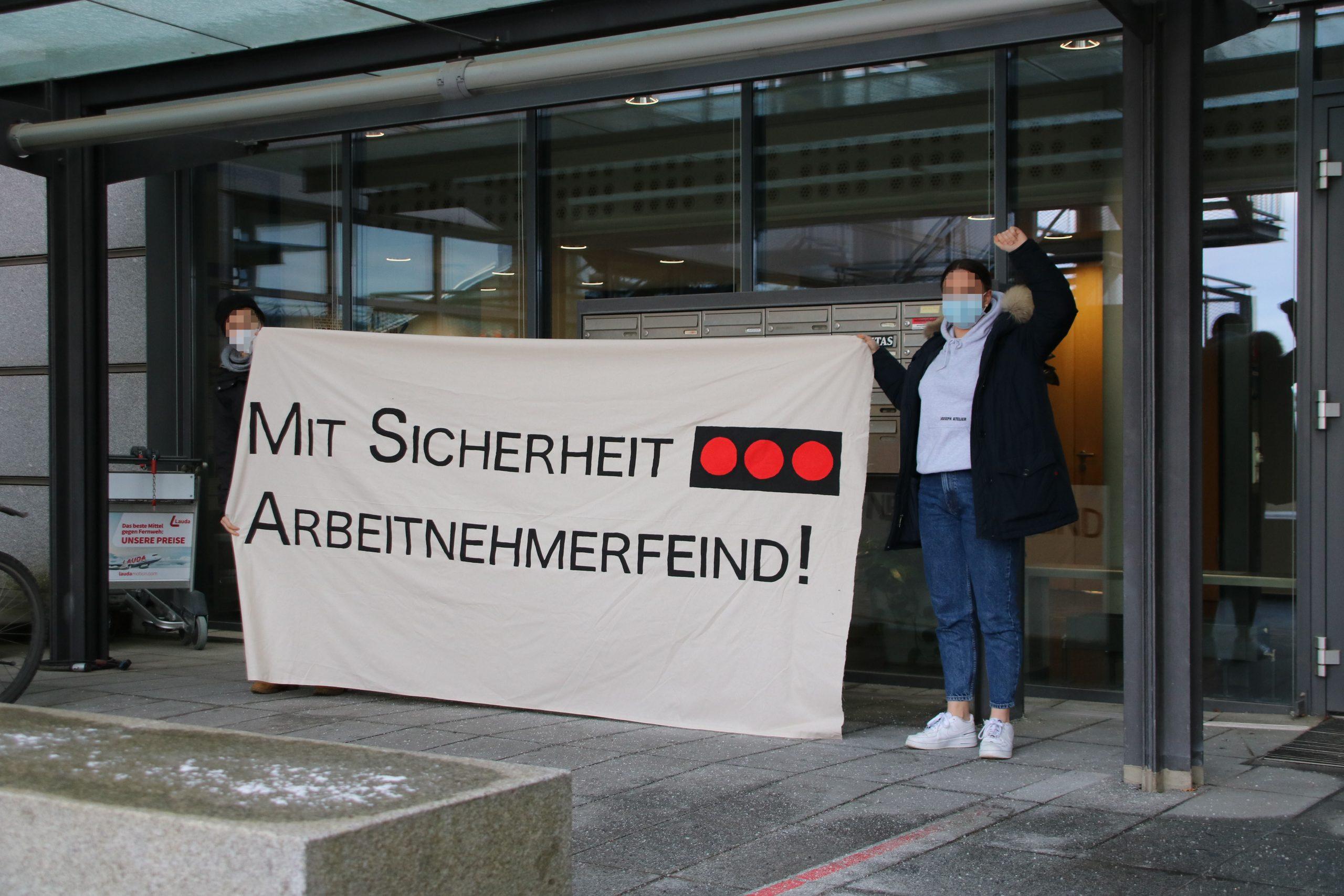 """Zwei Aktivistinnen stehen vor der Geschäftsstelle von Securitas in Stuttgart. Sie halten ein Transparent mit der Aufschrift """"Mit Sicherheit Arbeitnehmerfeind"""" und dem Logo von Securitas"""